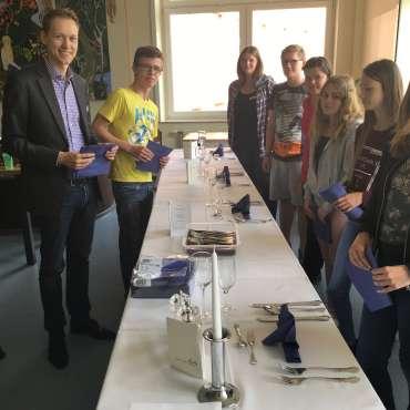 Alexander Trau mit Schülern beim Eindecken einer Tafel